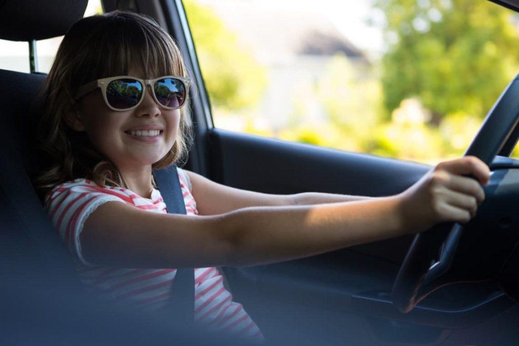 девочка за рулем улыбается